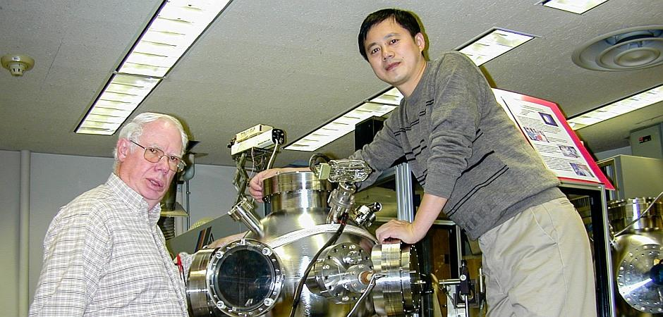 Mr. Li Chen, a PhD doctoral student, with Professor Cadieu<br>peer into a vacuum system designed for the simultaneous<br>deposition of thin films by pulsed laser deposition and sputtering